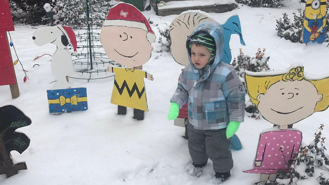 A little one hangs out in the snow with the Peanuts gang.