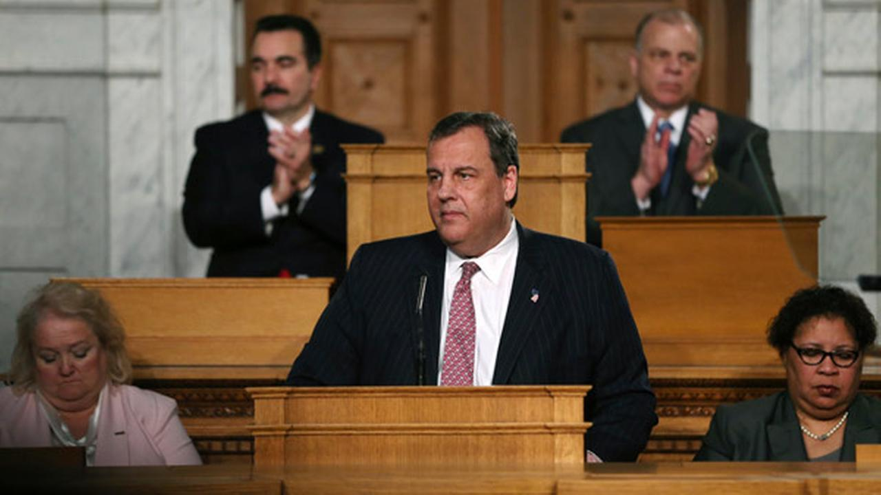 Vincent Prieto, left, Speaker of the New Jersey General Assembly and Steve Sweeney, right, New Jersey Senate President applaud as New Jersey Gov. Chris Christie.