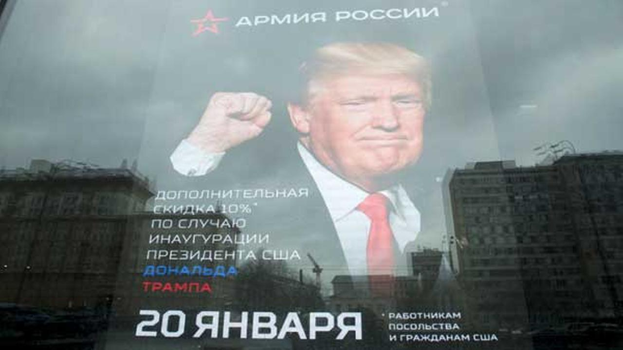 The U.S. Embassy building is reflected in a window of a Russian military outerwear shop Armia Rossii (Russian Army) displaying a poster of Donald Trump, in downtown Moscow.