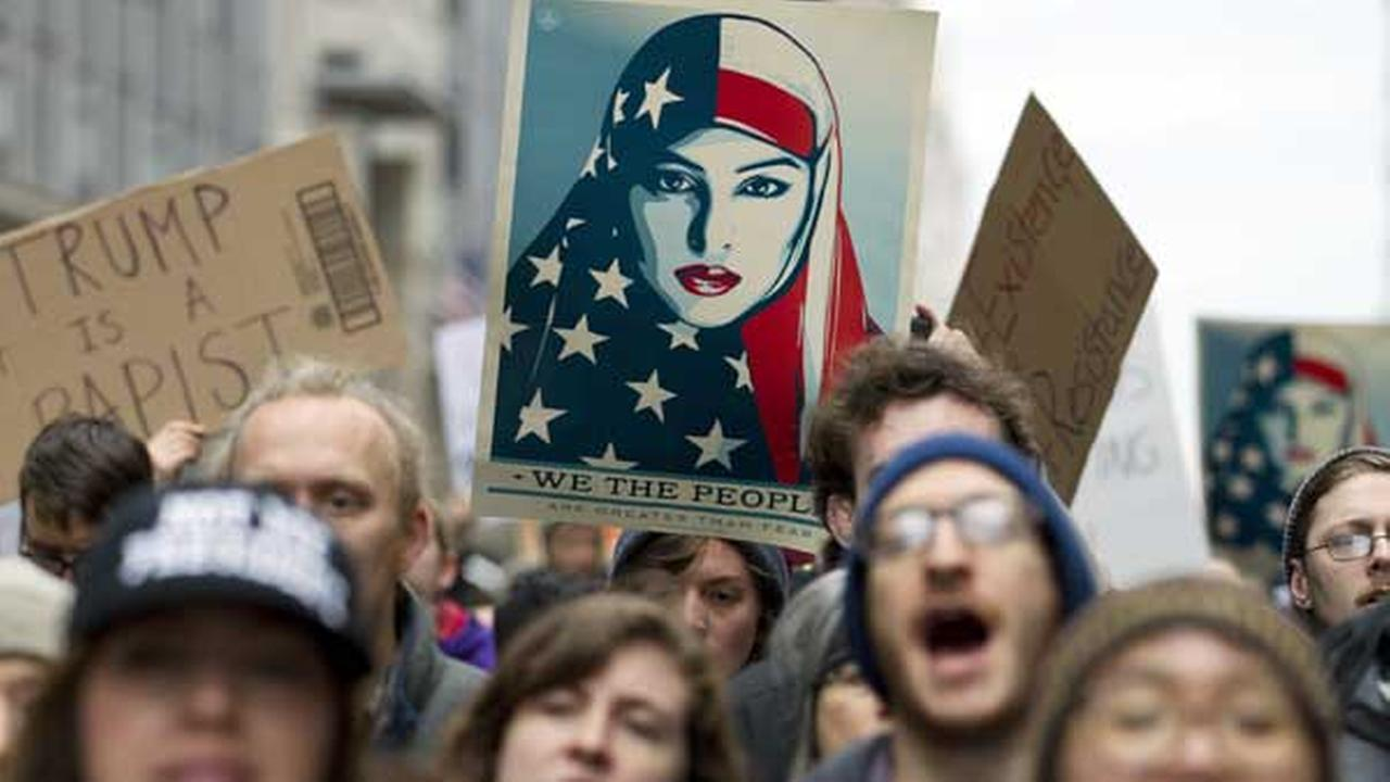Demonstrators march on the street near a security checkpoint inaugural entrance, Friday, Jan. 20, 2017 in Washington, ahead of President-elect Donald Trumps inauguration.