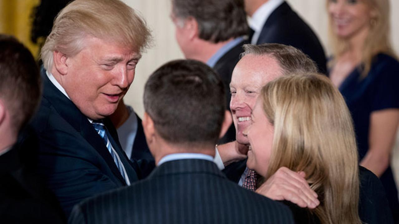 President Donald Trump, left, congratulates White House Press Secretary Sean Spicer, second from right, and other White House senior staff during a swearing in ceremony.