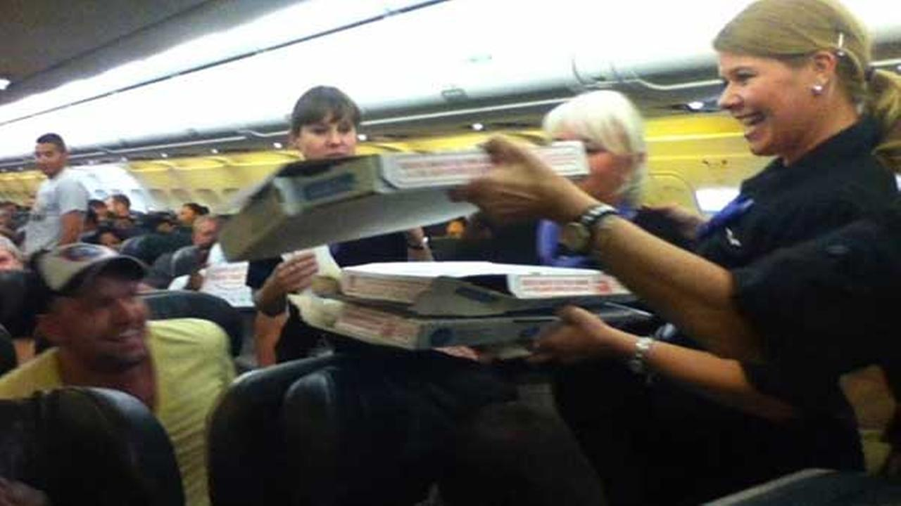 In this photo taken Monday, July 7, 2014, a Frontier Airlines flight attendant passes out pizza to passengers aboard a Denver-bound flight diverted to Cheyenne, Wyoming.
