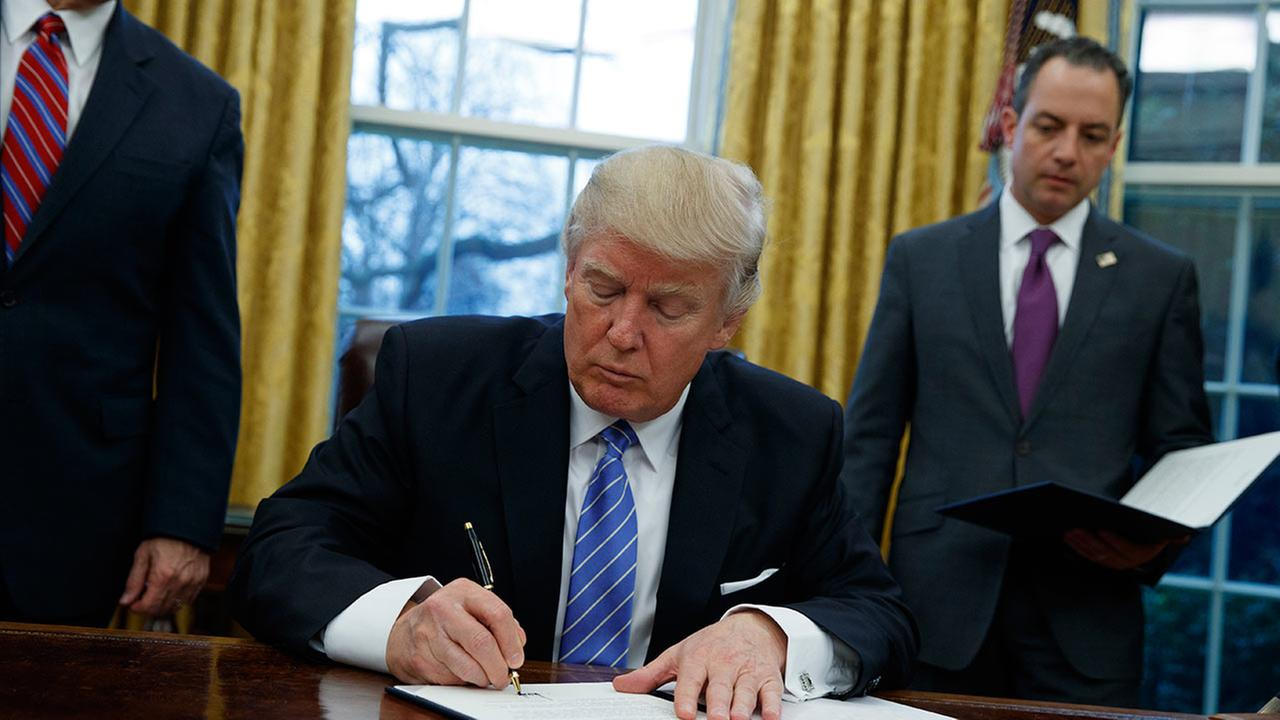President Donald Trump signs an executive order to withdraw the U.S. from the 12-nation Trans-Pacific Partnership trade pact, Monday, Jan. 23, 2017.