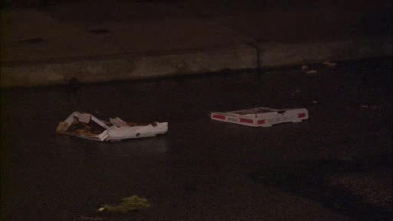 Pizza boxes are seen on the road after a shooting in Southwest Philadelphia.