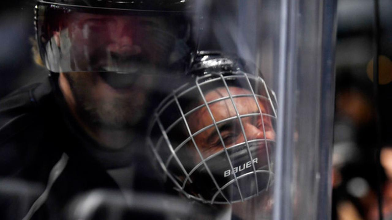Singer Justin Bieber, who is playing for Team Gretzky, is pushed into the glass by Chris Pronger of Team Lemieux during the first period of the NHL All-Star Celebrity Shootout.