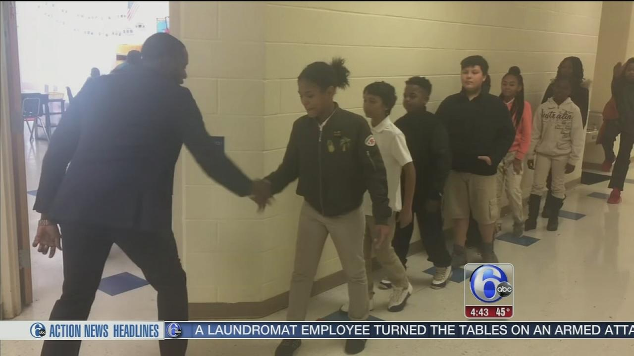 Teacher begins class with unique handshake for each student