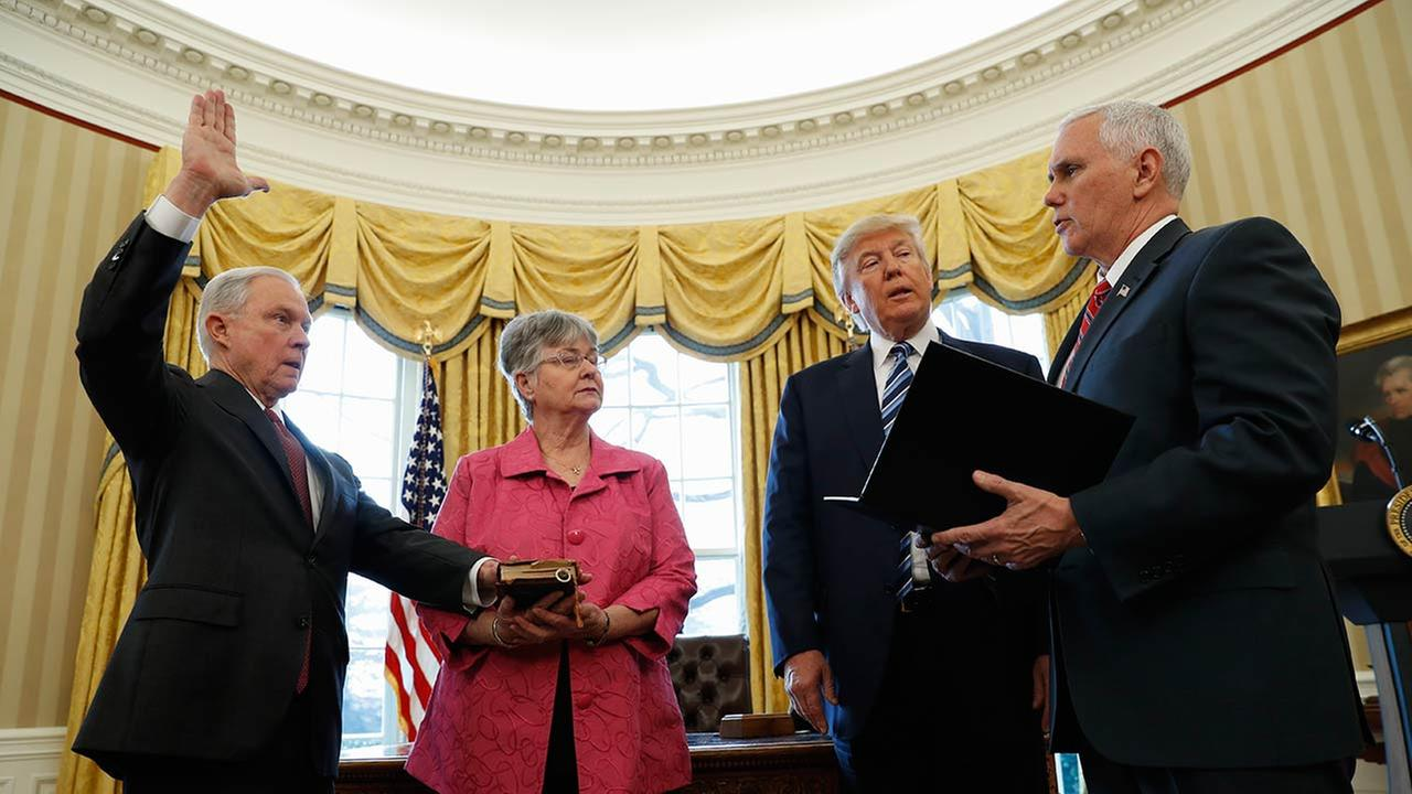 President Donald Trump watches as Vice President Mike Pence administers the oath of office to Attorney General Jeff Sessions, accompanied by his wife Mary, Thursday, Feb. 9, 2017.
