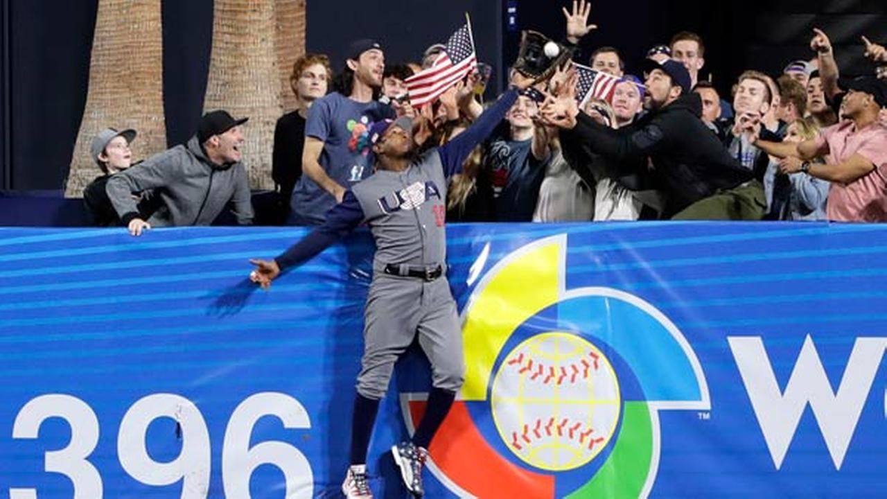 United States outfielder Adam Jones grabs a catch above the wall for the out on the Dominican Republics Manny Machado during a second-round World Baseball Classic baseball game.