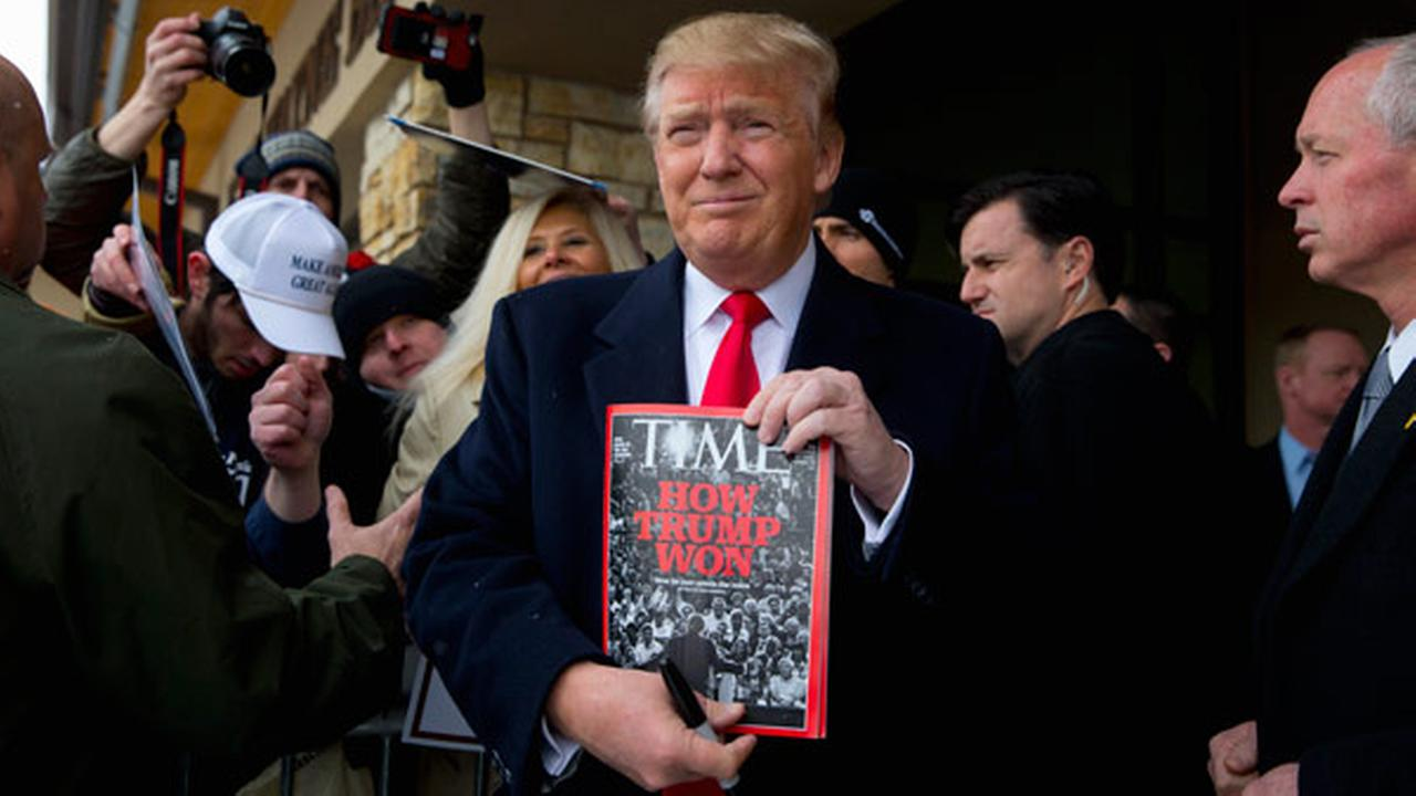 In this Jan. 19, 2016, photo, Republican presidential candidate Donald Trump holds a Time magazine featuring an article on him outside the John Wayne Museum in Winterset, Iowa.