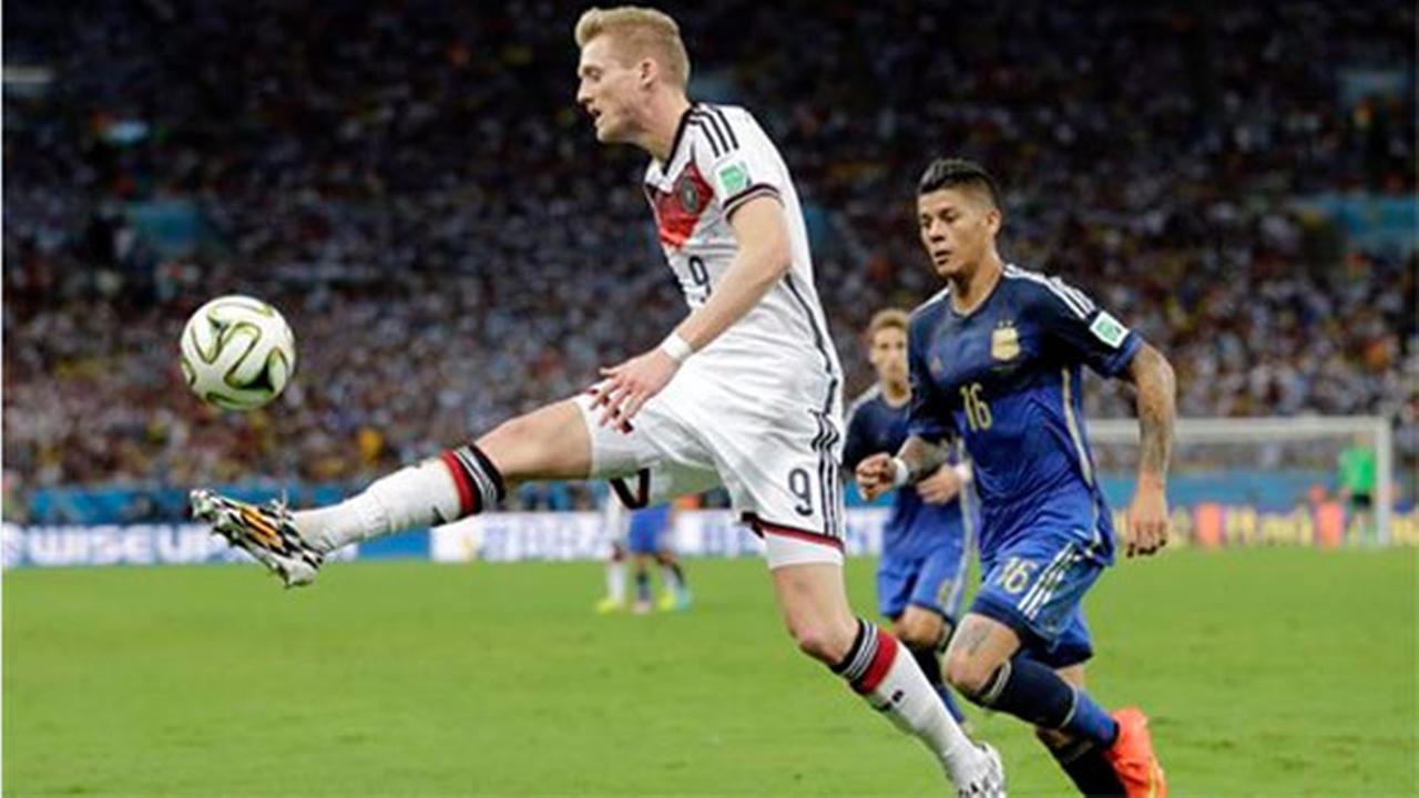 Germanys Andre Schuerrle (9) controls the ball ahead of Argentinas Marcos Rojo (16) during the World Cup final soccer match, Sunday, July 13, 2014.