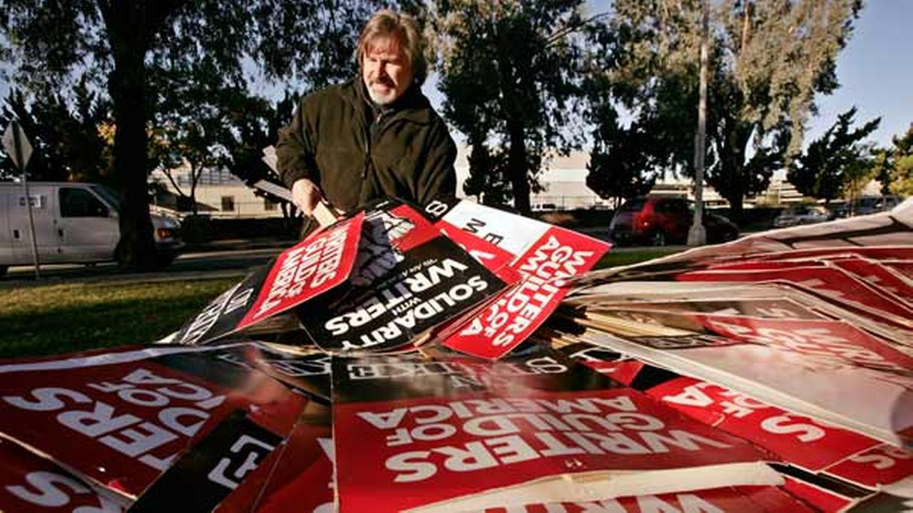 Peter Sears, a writer with The Tonight Show with Jay Leno, gathers signs to distribute to striking film and television writers, Tuesday, Dec. 4, 2007, in Burbank, Calif.