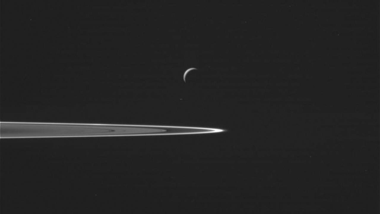 This Wednesday, Oct. 28, 2015 image provided by NASA shows Saturns moon Enceladus, center, as the Cassini spacecraft prepared to make a close flyby of the icy moon.