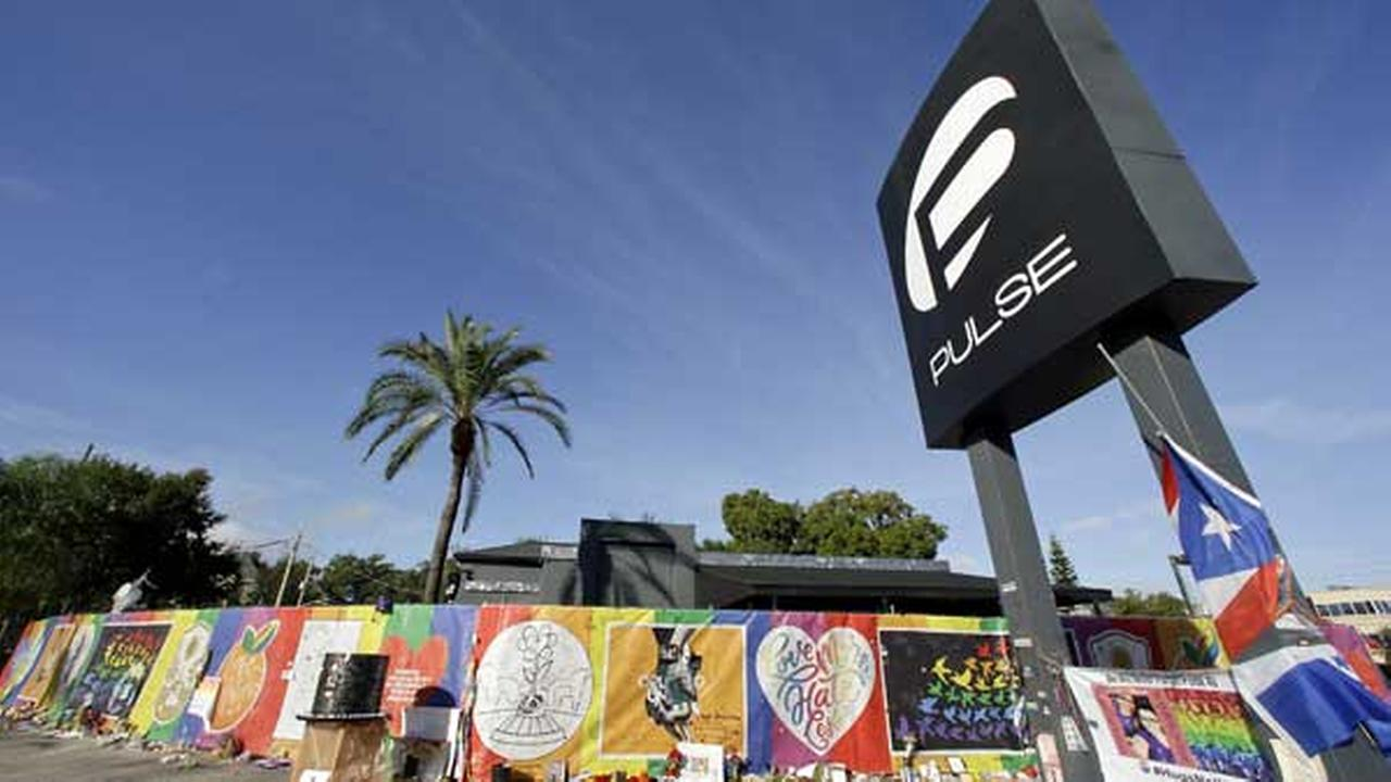 FILE - In this Nov. 30, 2016 file photo, artwork and signatures cover a fence around the Pulse nightclub, scene of a mass shooting, in Orlando, Fla.