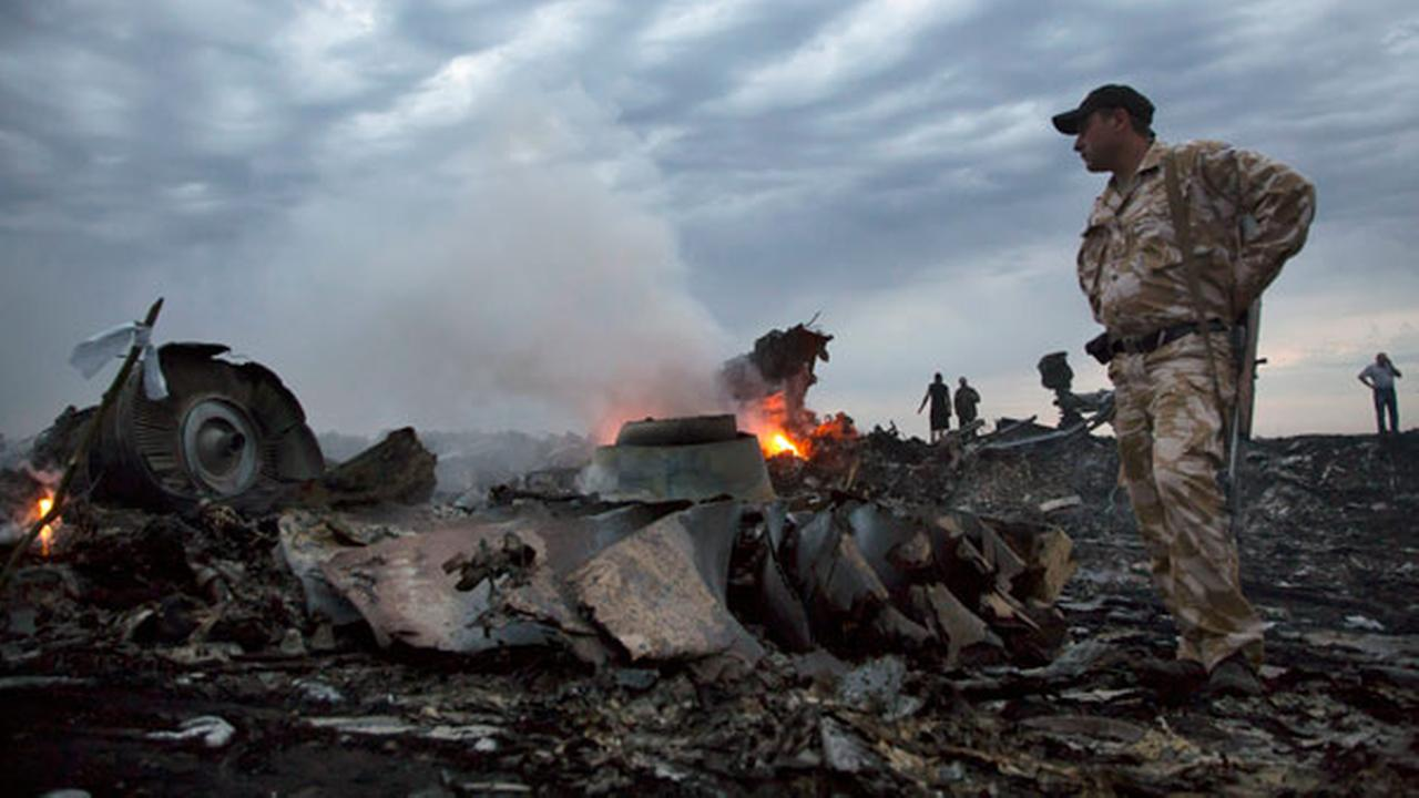 People walk amongst the debris, at the crash site of a passenger plane near the village of Grabovo, Ukraine, Thursday, July 17, 2014.