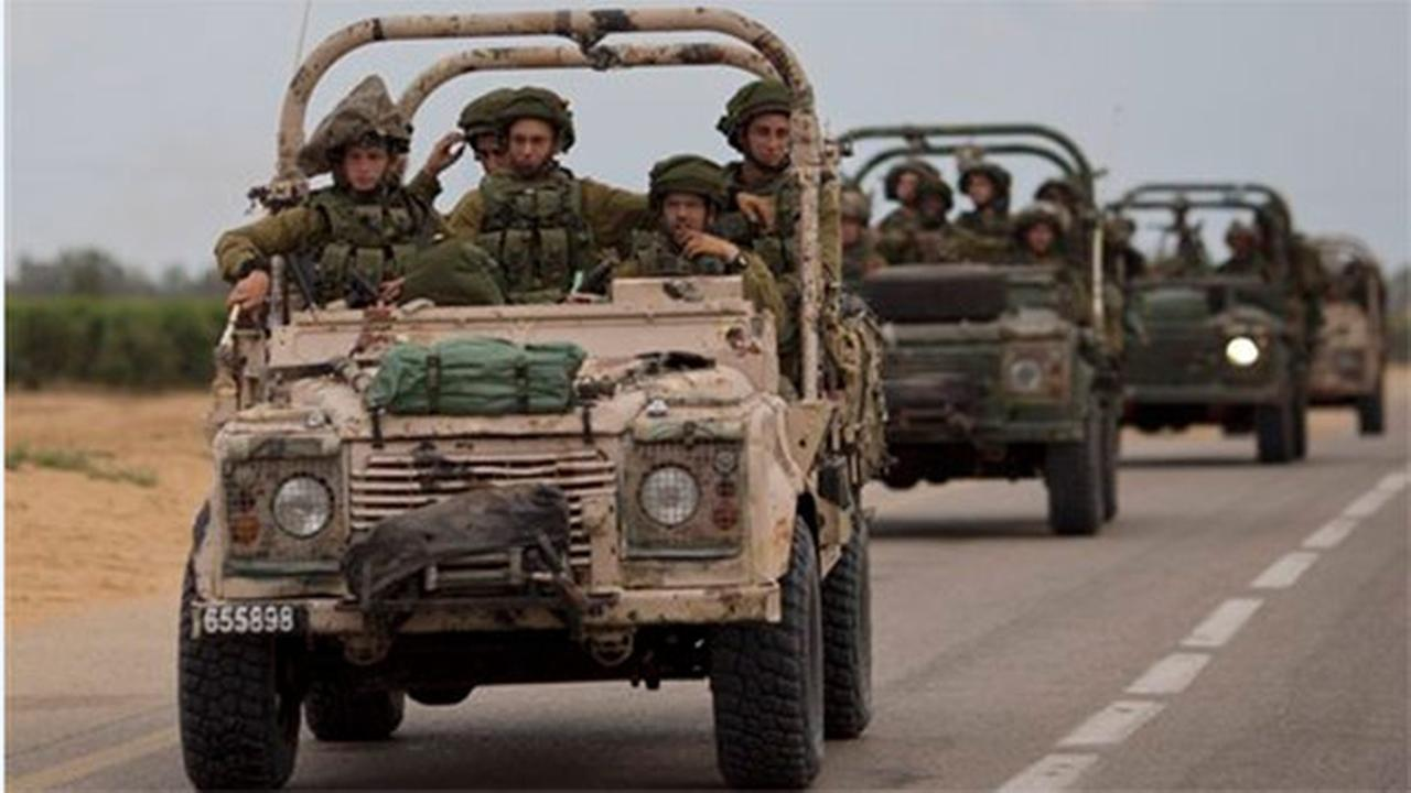 Israeli soldiers ride on a military vehicle near the Israel-Gaza Border, Thursday, July 17, 2014.