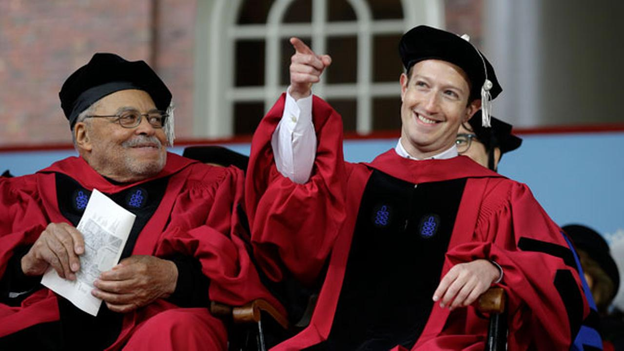 Facebook CEO and Harvard dropout Mark Zuckerberg, right, gestures as actor James Earl Jones, left, looks on while seated on stage during Harvard University commencement exercises.