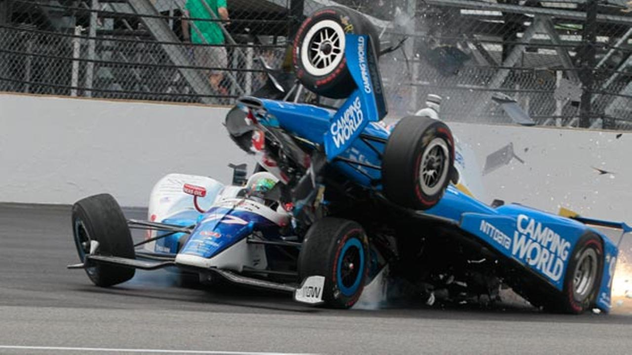Scott Dixon, of New Zealand, begins to go over the top of Jay Howard, of England, during the running of the Indianapolis 500 auto race at Indianapolis Motor Speedway.