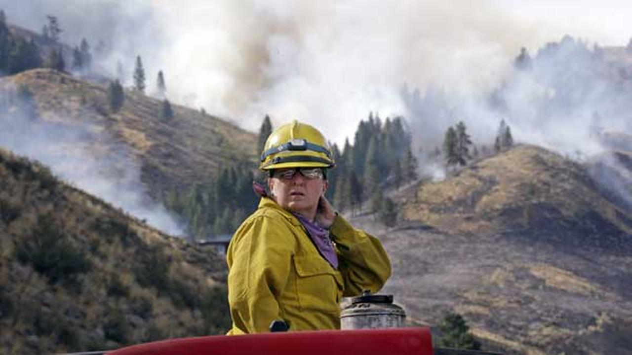 Firefighter Kathleen Calvin looks around as she sits atop her fire truck while waiting to begin work as smoke from a wildfire fills the sky behind Saturday, July 19, 2014.