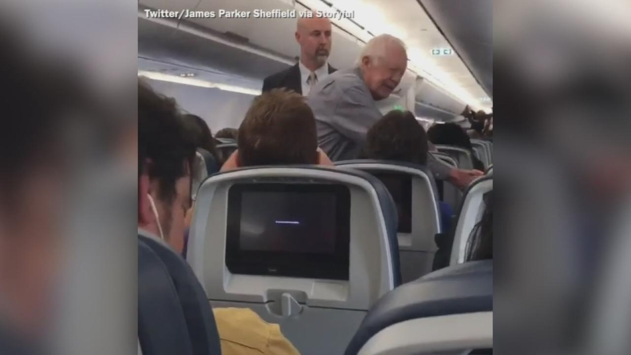 Former US President Jimmy Carter shakes hands with flight passengers