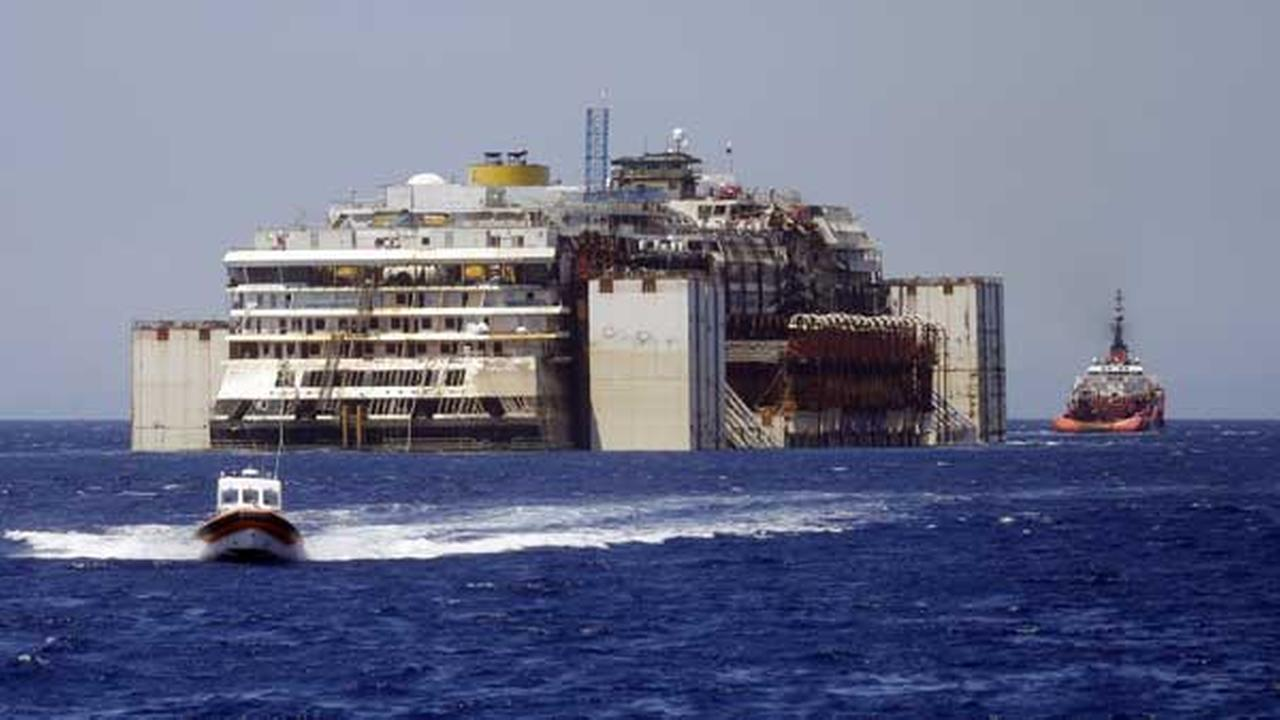 The wreck of the Costa Concordia cruise ship is towed by two tugboats as it leaves behind the tiny Tuscan island of Isola del Giglio, Italy, Wednesday, July 23, 2014.