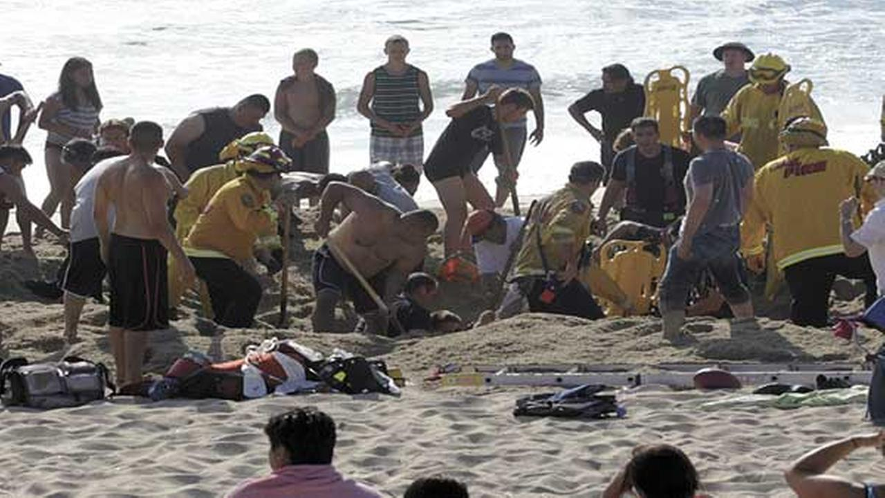This Monday, July 21, 2014, photo released by the Half Moon Bay Review shows emergency crew workers and volunteers working to rescue a man at Francis State Beach in Half Moon Bay.