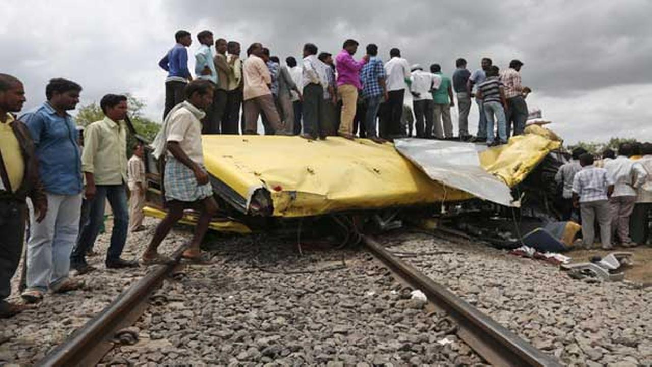 Indians stand on top of a bus that was crushed when a train crashed into it in Medak district in the southern Indian state of Telangana, Thursday, July 24, 2014.