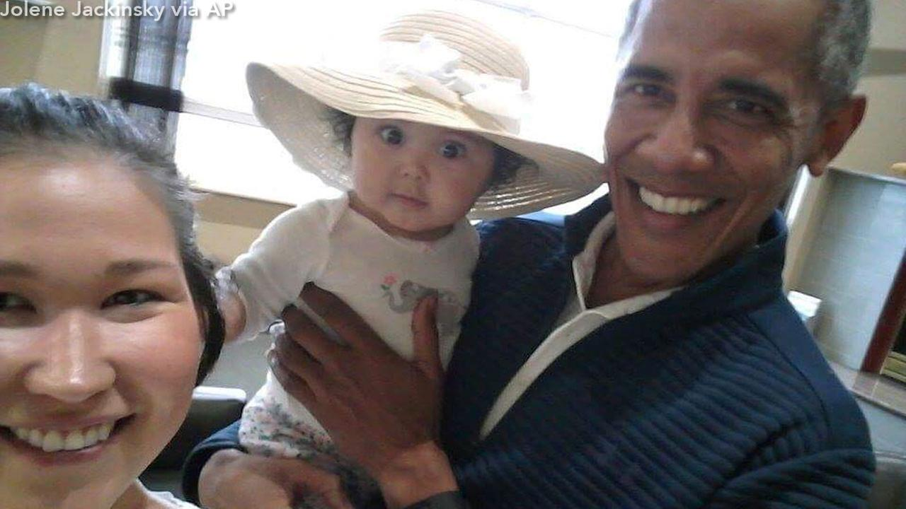 An Alaska mother is cherishing cellphone photos she snapped of her wide-eyed 6-month-old baby in the arms of former President Barack Obama.