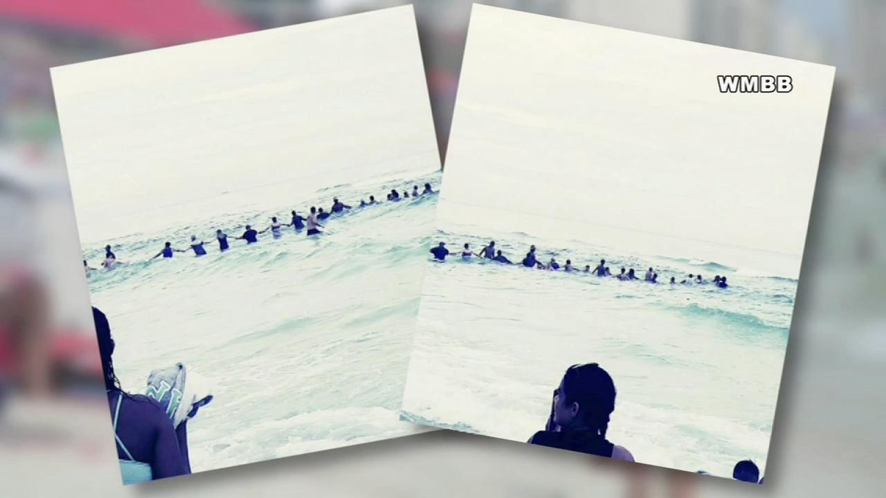 VIDEO: Beachgoers form human chain to rescue family in water