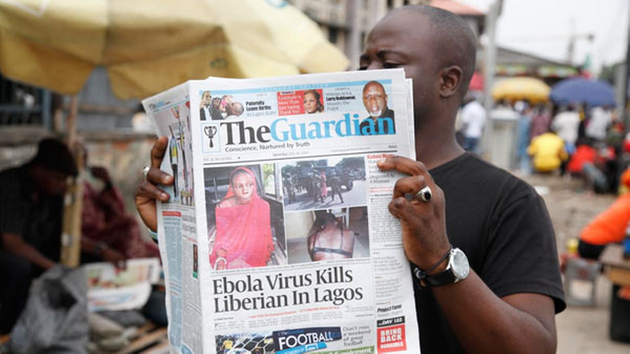 A man reads a newspaper on a Lagos street with the headline Ebola Virus kills Liberian in Lagos, Saturday, July 26, 2014.