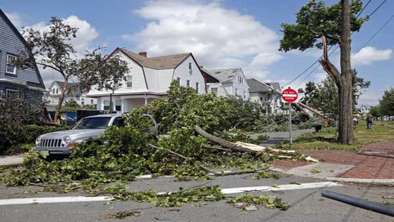 Downed trees and power lines lay in front of homes in Revere, Mass., Monday, July 28, 2014 after a tornado touched down.
