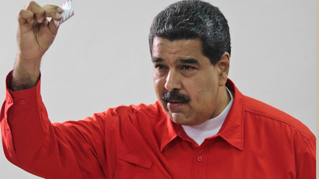 In this photo released by Miraflores Press Office, Venezuelas President Nicolas Maduro shows his ballot after casting a vote for a constitutional assembly in Caracas, Venezuela.