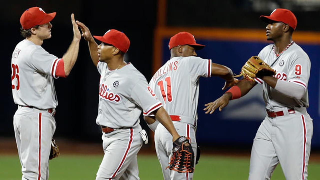 Philadelphia Phillies Chase Utley, left, Ben Revere, second from left, Jimmy Rollins, and Domonic Brown, right, celebrate after a baseball game against the New York Mets.