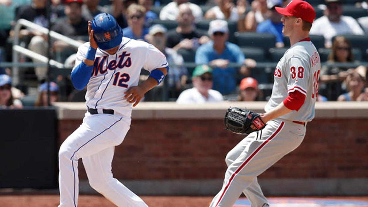 New York Mets Juan Lagares (12) scores on Philadelphia Phillies starting pitcher Kyle Kendricks fifth-inning, wild pitch as Kendrick (38) covers the plate in a baseball game.