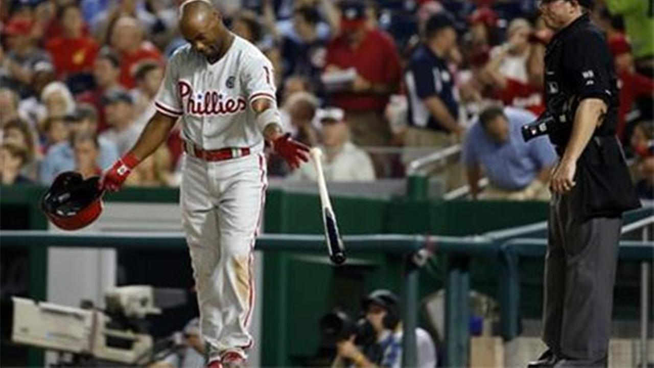 Philadelphia Phillies Jimmy Rollins tosses his bat and helmet after being called out on a called third strike against the Washington Nationals on Friday, Aug. 1, 2014