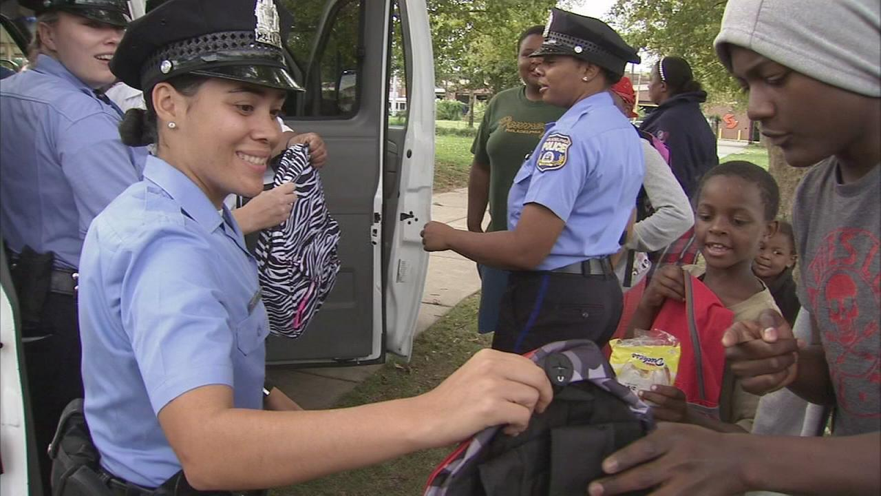Philadelphia Police officers hand out backpacks in West Philadelphia