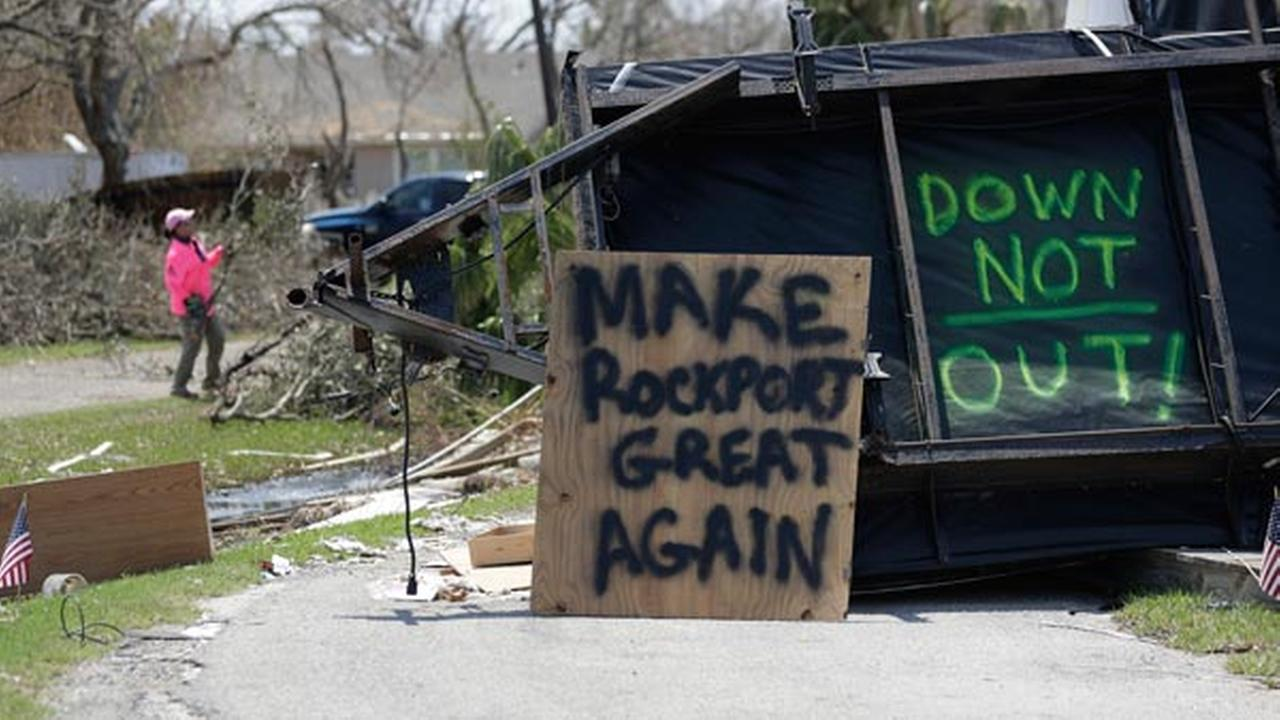 In this Sept. 2, 2017, photo, the messages Make Rockport Great Again and Down Not Out are written at a destroyed home in Rockport, Texas.