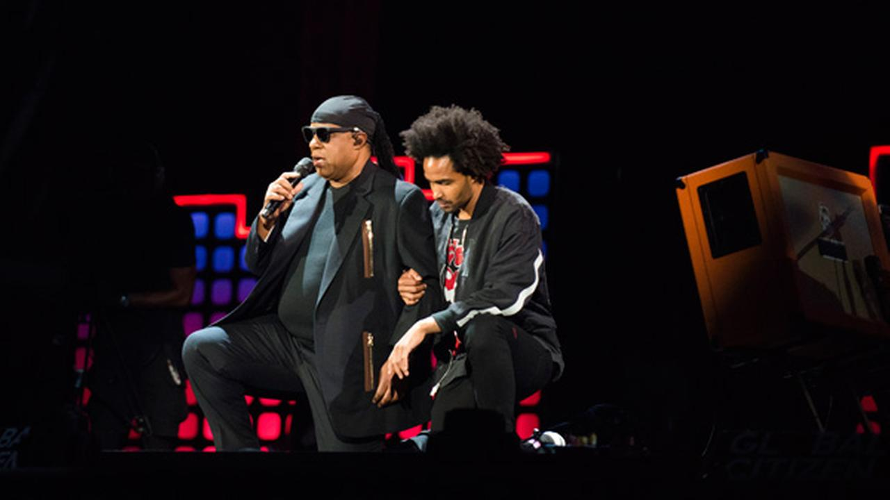 Stevie Wonder, left, takes a knee for the country with his son, Kwame Morris, before performing at the 2017 Global Citizen Festival in Central Park, Saturday, Sept. 23, 2017.