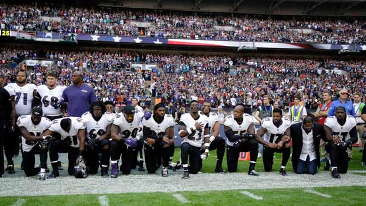 Baltimore Ravens players, including retired linebacker Ray Lewis (second on the right) kneel during the performance of the pre-game national anthem in London.