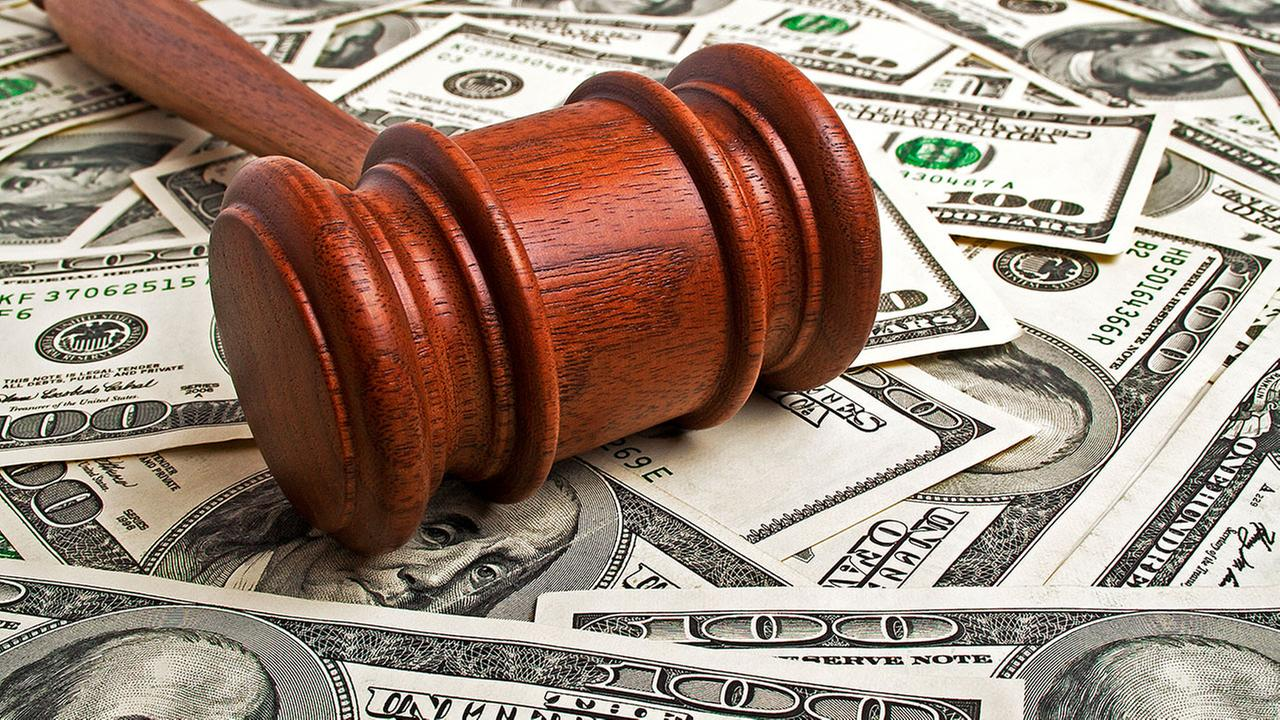Stock photo of wooden gavel laying on American dollars