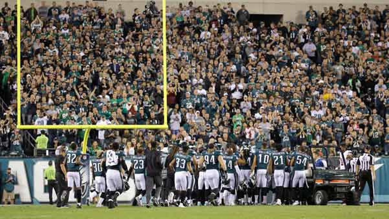 Philadelphia Eagles players gather on the field as teammate Jason Peters is put on a cart and taken off the field.