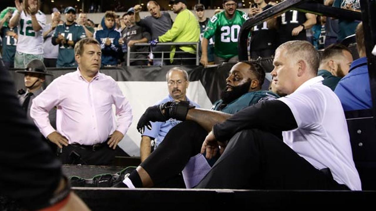 Fans cheer as Philadelphia Eagles offensive tackle Jason Peters, second from bottom right, is carted off the field.