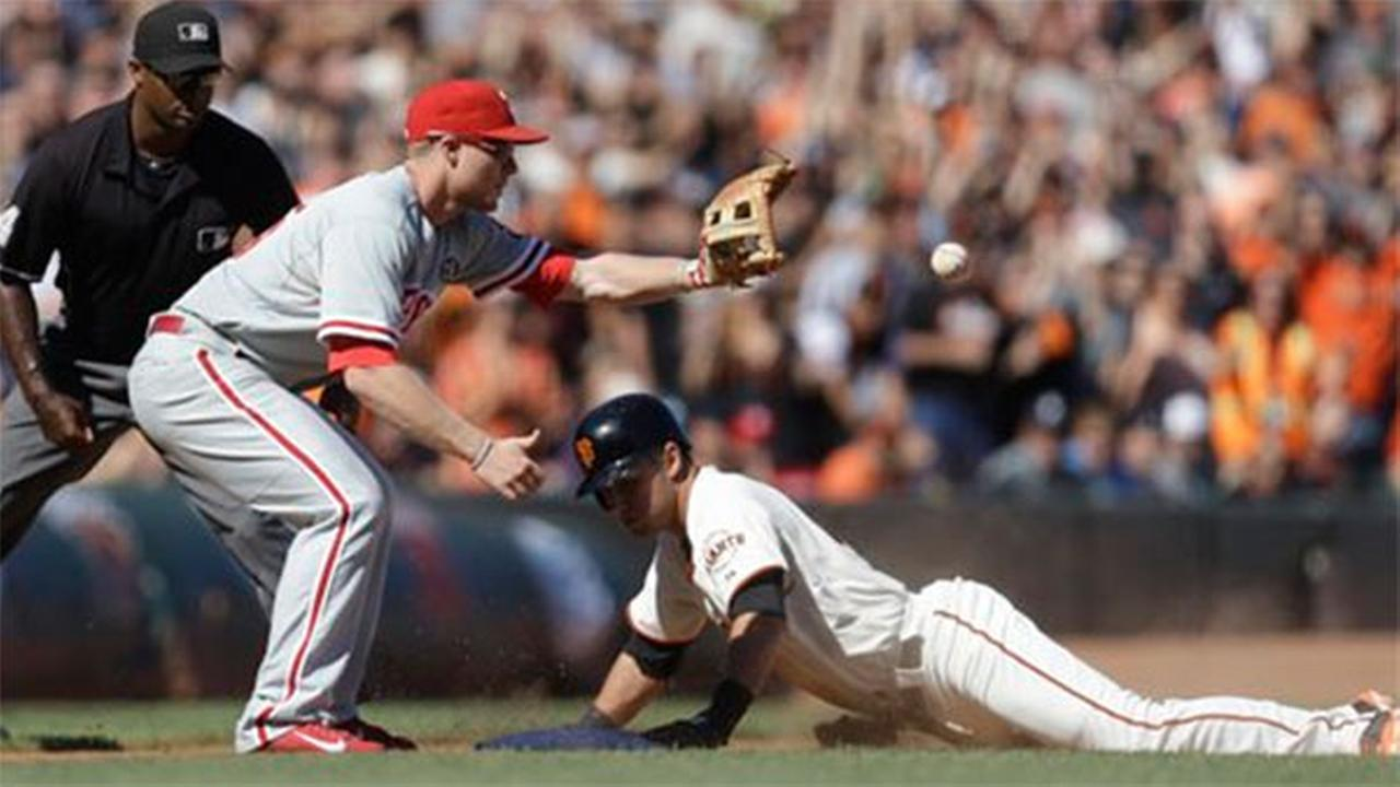 San Francisco Giants Joe Panik, right, slides safe beneath the ball and Philadelphia Phillies third baseman Cody Asche, Saturday, Aug. 16, 2014.