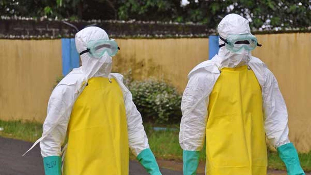 Health workers wearing protective gear go to remove the body of a person who is believed to have died after contracting the Ebola virus in the city of Monrovia, Liberia.