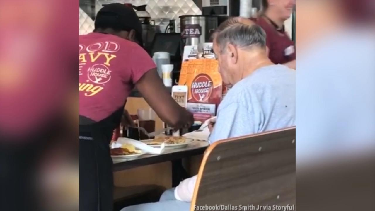 Diner cook cuts up food for man with arm injury