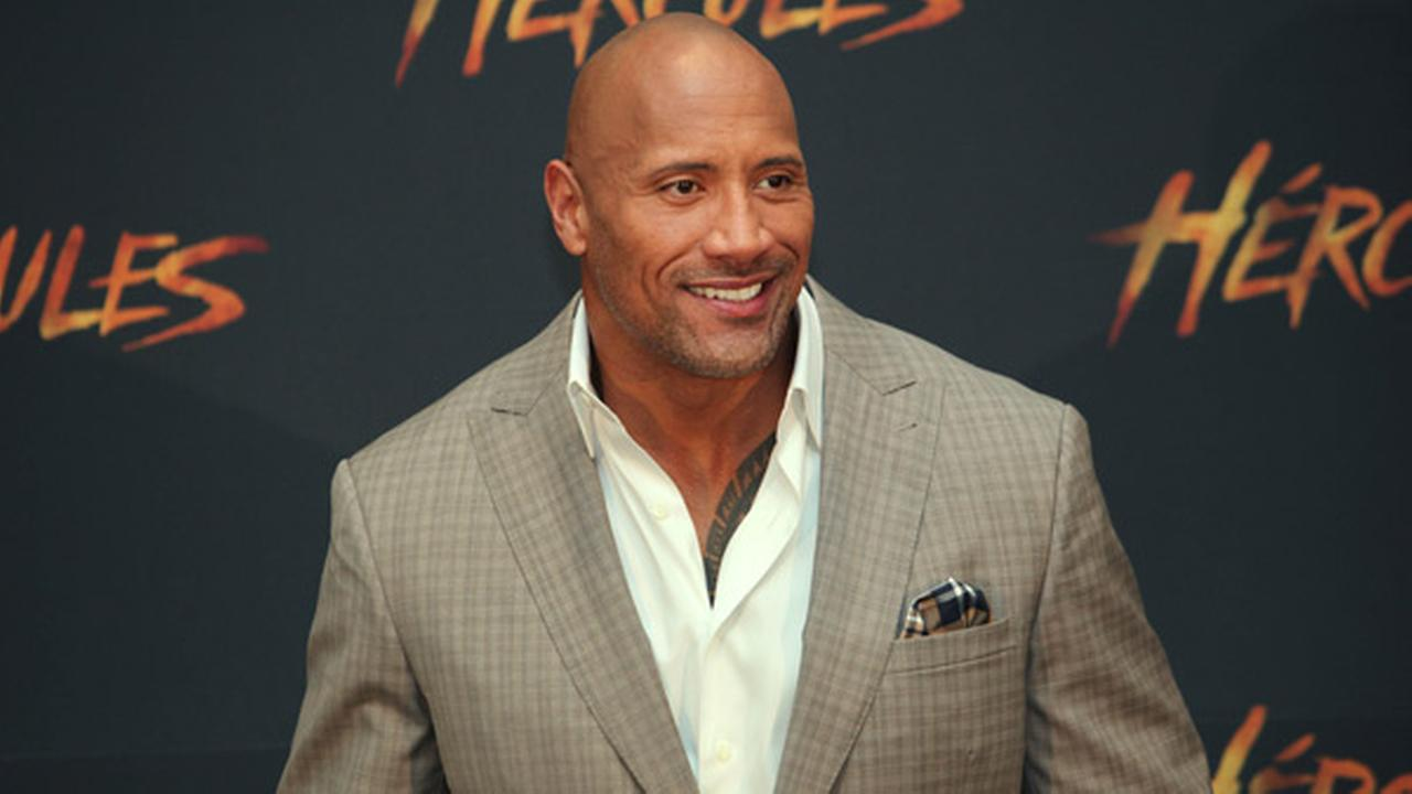U.S. actor Dwayne Johnson poses for photos as he arrives for an event to promote his film Hercules, in Mexico City, Monday, August 18, 2014.