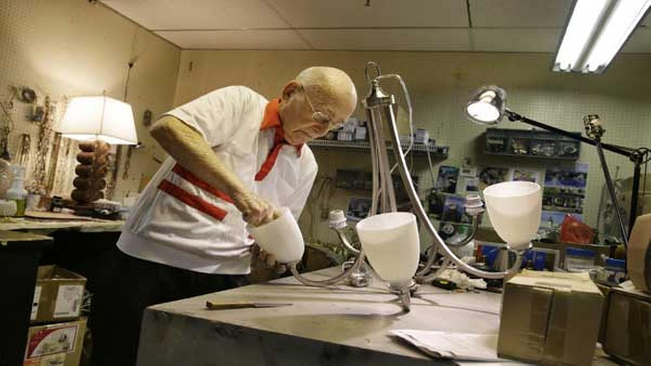 Lighting repair specialist Herman Hy Goldman, 101, refurbishes a light fixture in his workshop at Capitol Lighting where he has worked for 73 years, Monday, Aug. 18, 2014.