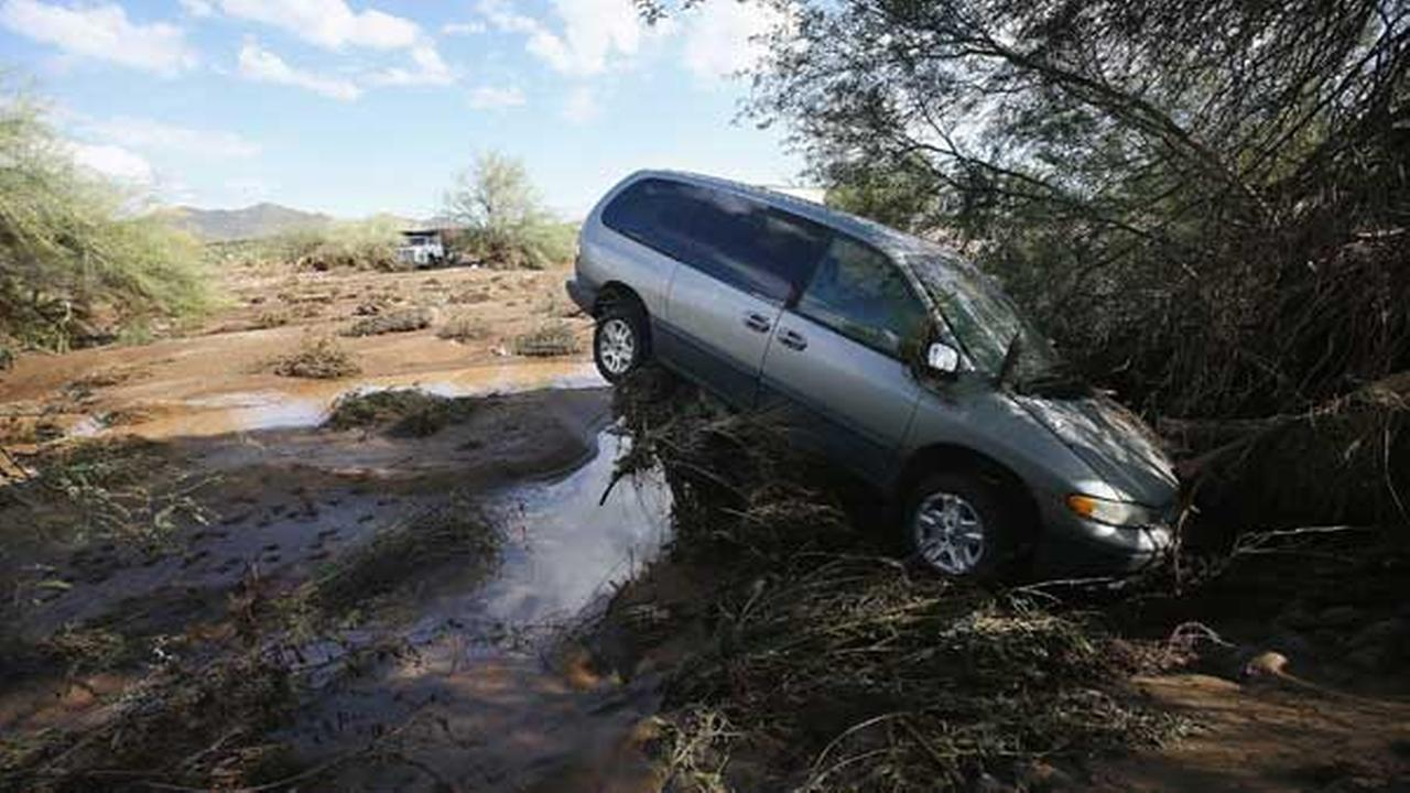 A vehicle sits atop debris where flash flood waters pushed it after rising waters overran Skunk Creek after strong storms moved through, Tuesday, Aug. 19, 2014.