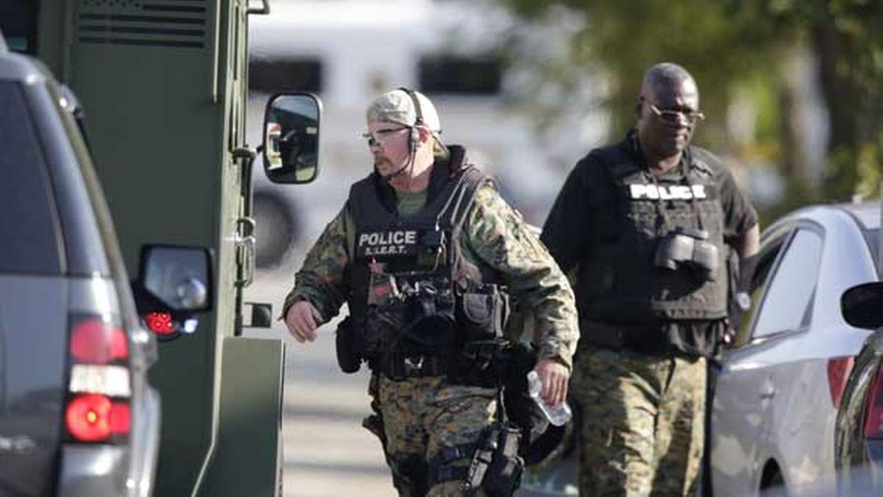 Police don body armor as authorities negotiate with two men who are barricaded in a home and holding a woman and five children hostage in the south suburb of Harvey, Ill.