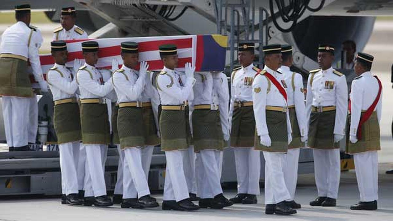 Malaysian Army soldiers carry a coffin containing one of the bodies of the downed MH17 flight upon arrival at Kuala Lumpur International Airport in Sepang, Malaysia.