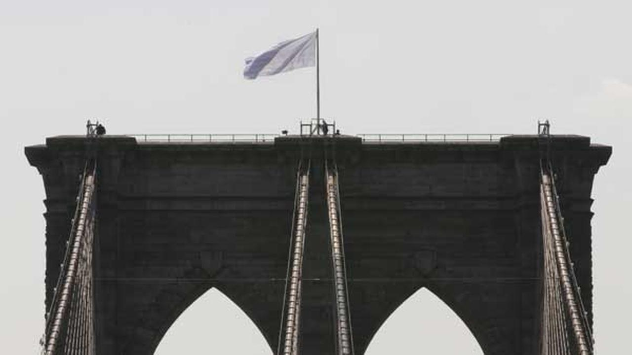 FILE - In a Tuesday, July 22, 2014 file photo, New York City Police officers stand at the base of a white flag flying atop the west tower of the Brooklyn Bridge.